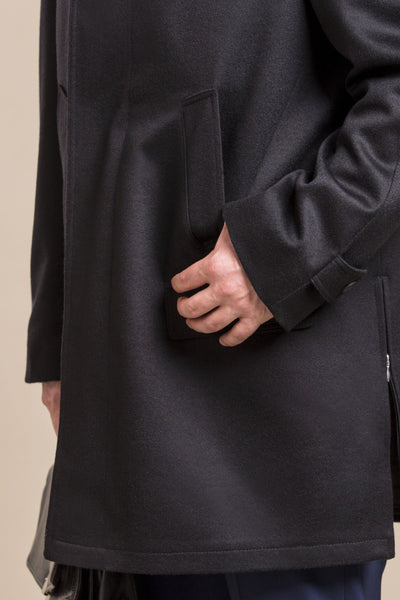 a close up view of the hand in a pocket of a 30 year old man wearing an austrian himalaya loden wool overcoat
