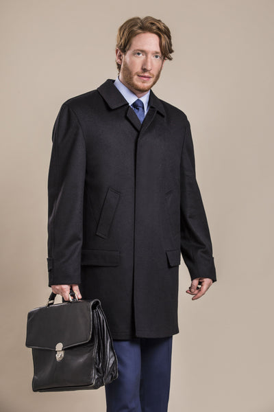 a side view of a 30 year old man wearing an austrian himalaya loden wool overcoat