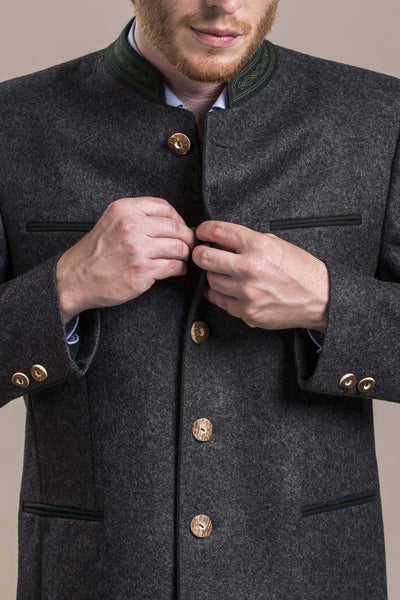 a front view of a 30 year old man buttoning an austrian loden wool jacket