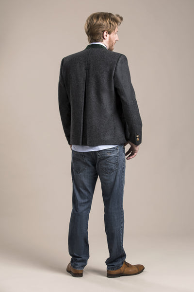 a backside view of a 30 year old man wearing an austrian loden wool jacket