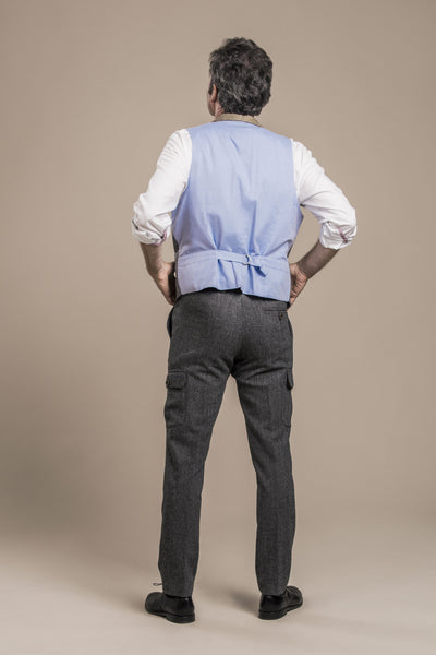 a backside view of a 50 year old man wearing an austrian loden wool vest with austrian loden wool pants