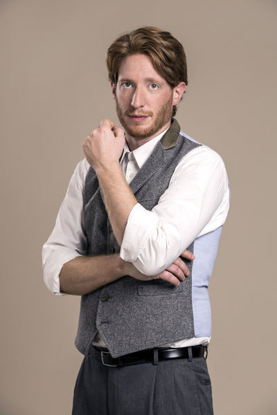 a frontal bust view of a 30 year old man wearing an austrian loden wool vest with austrian loden wool pants