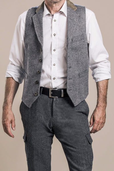 a frontal view of a 50 year old man wearing an austrian loden wool vest with austrian loden wool pants