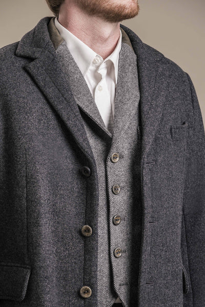 a frontal close up bust view without the head of a 30 year old man wearing an austrian loden wool vest with an austrian loden wool coat