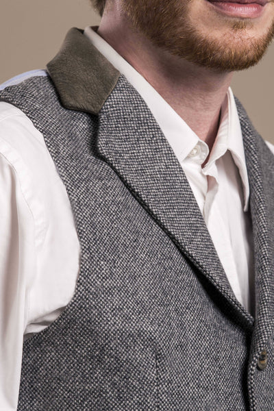a close up profile view of a 30 year old man wearing an austrian loden wool vest
