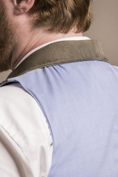 a backside close up view of a 30 year old man wearing an austrian loden wool vest