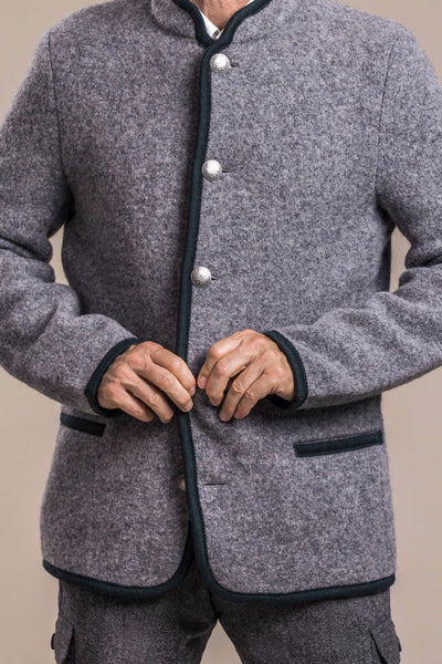 a frontal view of a 50 year old man wearing a gray traditional austrian boiled wool jacket