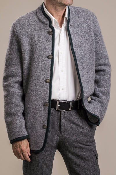 a frontal view of a 50 year old man with hand in pocket wearing a gray traditional austrian boiled wool jacket