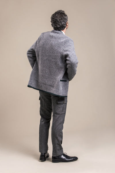 a full body backside view of a 50 year old man wearing a gray traditional austrian boiled wool jacket