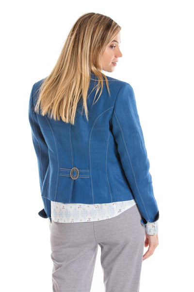 back view of a young blonde women wearing a blue Austrian linen riding jacket