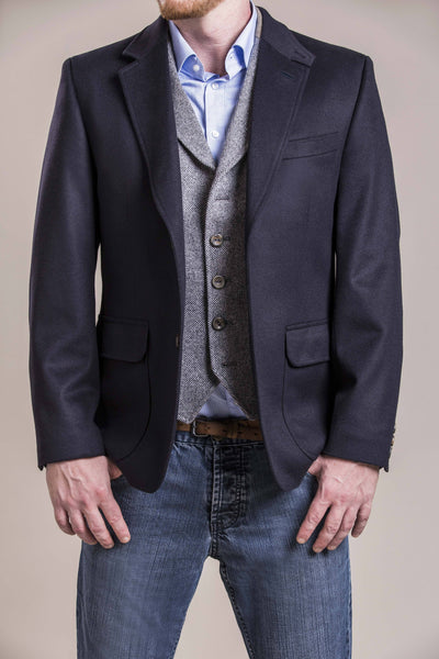 a frontal chest view of a 30 year old man wearing a wool blazer made from austrian himalya loden wool