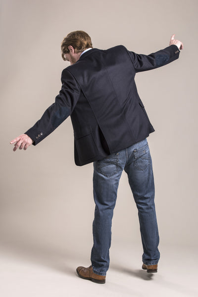 a backside view of a 30 year old man wearing a wool blazer made from austrian himalya loden wool