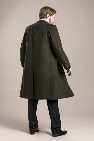 a backside view of a 30 year old man wearing a green austrian loden coat made from himalaya loden wool