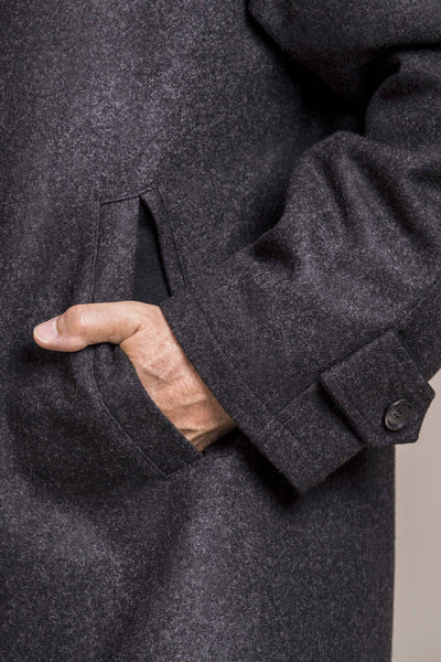 a close up view of the hand in a pocket of a 30 year old man wearing a wool coat with zipper and button flap made of 100% virgin loden wool
