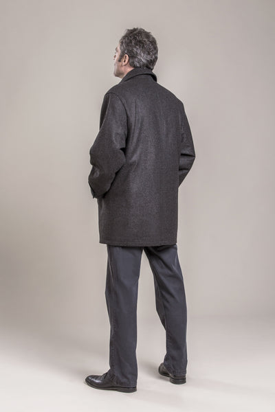 a backside view of a 50 year old man wearing a wool coat with zipper and button flap made of 100% virgin loden wool