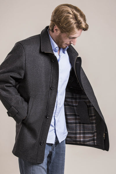 a frontal view of a 30 year old man wearing a wool coat with zipper and button flap made of 100% virgin loden wool