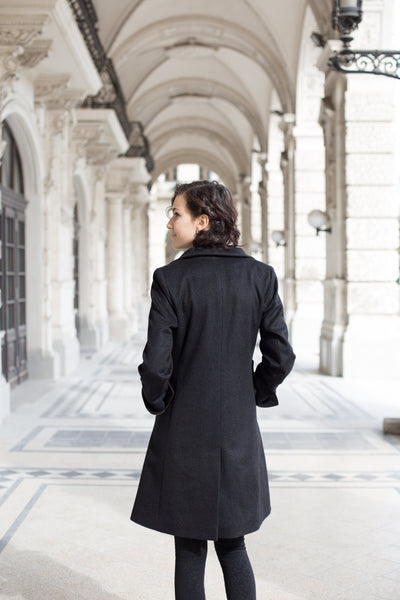 female model in a charcoal color loden wool coat showing the back of the coat