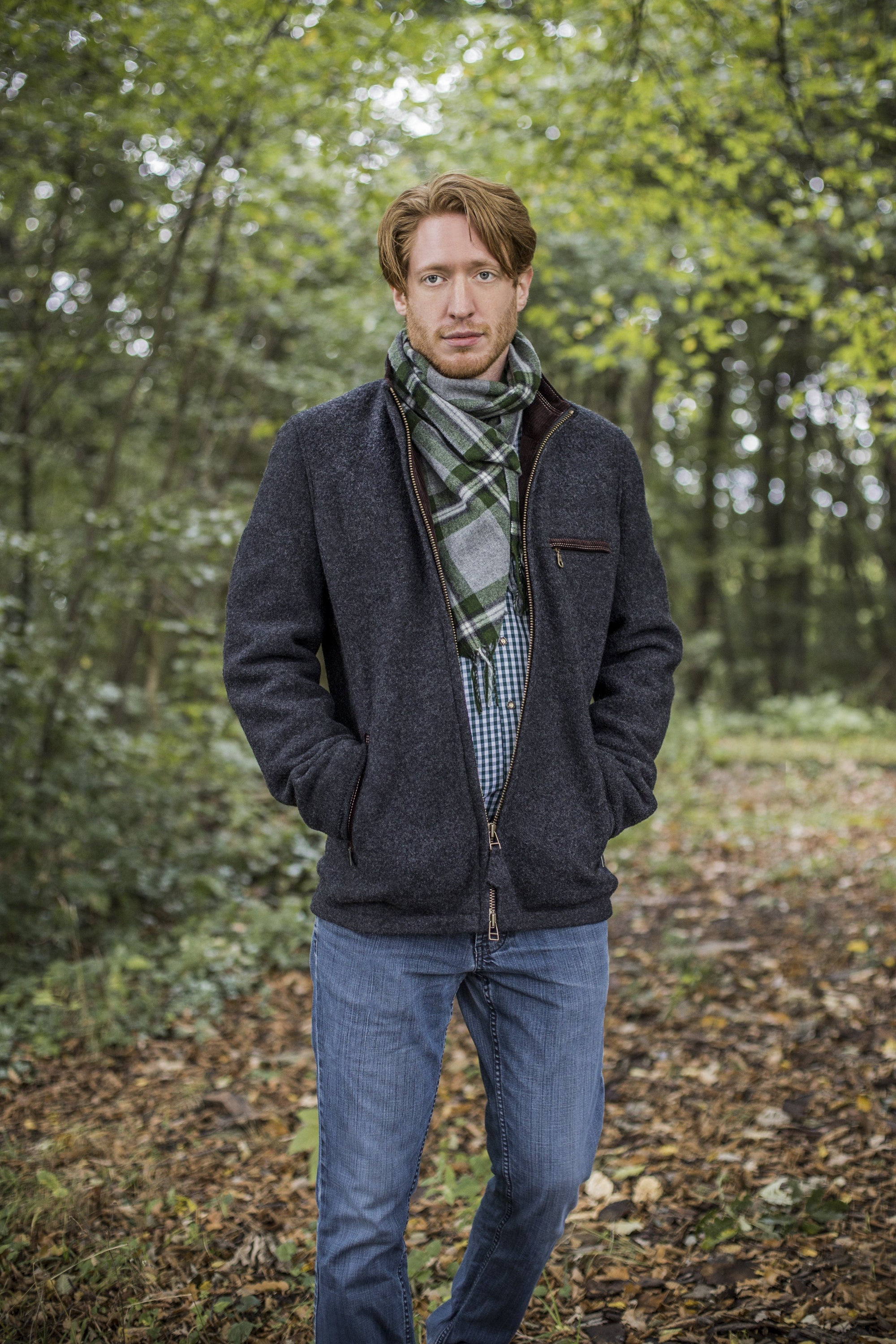 view of a 30 year old man wearing a contemporary austrian wool walk jacket with zipper in the forest