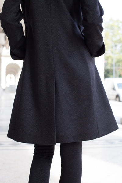backside portrait of a female model in a charcoal color loden wool coat