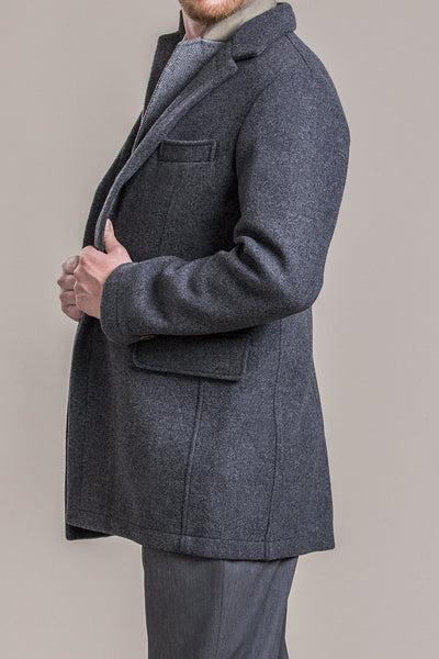 a side view of a 30 year old man wearing a 100% virgin austrian loden wool coat over a loden wool vest and loden wool pants