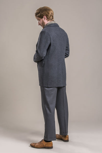 a side backside view of a 30 year old man wearing a 100% virgin austrian loden wool coat over a loden wool vest and loden wool pants