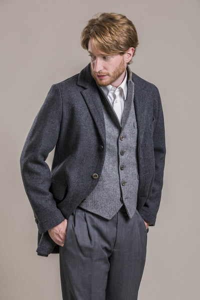 a frontal view of a 30 year old man looking away from the camera wearing a 100% virgin austrian loden wool coat over a loden wool vest and loden wool pants