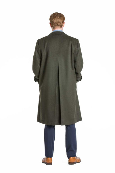 back view of a young man wearing a Robert W. Stolz green loden coat with removable zip out lining