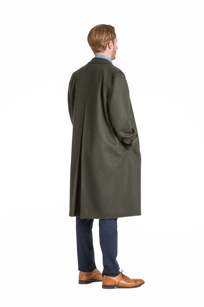 side view of a young man wearing a Robert W. Stolz green loden coat with removable zip out lining