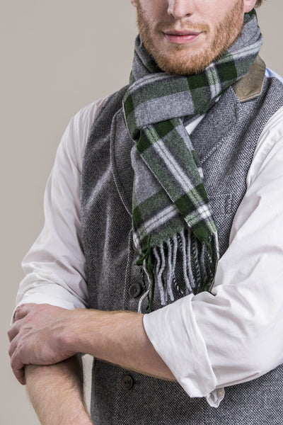 a close up of a 30 year old man wearing an austrian wool scarf and austrian loden wool pants