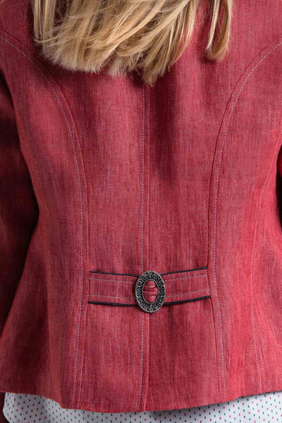 back view of a young blonde women wearing a red linen riding jacket