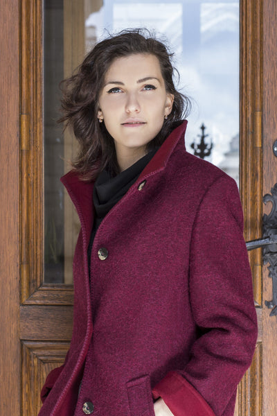 female model wearing a red wool coat in front of a wooden door made of an alpaca sheep wool loden blend