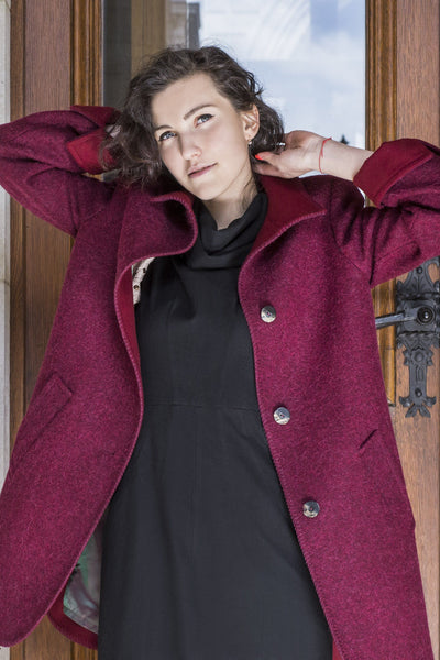 female model wearing a red wool coat in Vienna made of an alpaca sheep wool loden blend