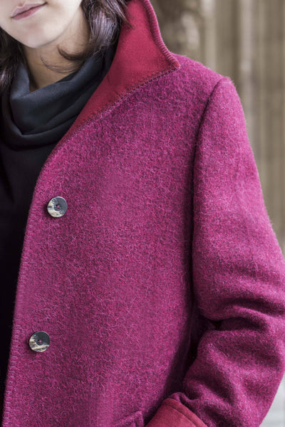 a close up female model wearing a red wool coat made of an alpaca sheep wool loden blend