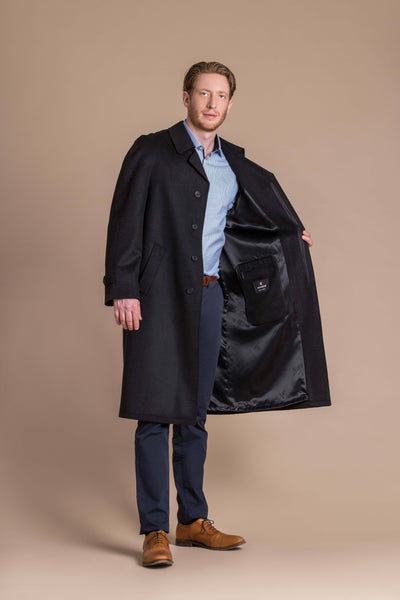 man wearing a full length loden wool coat with raglan sleeves