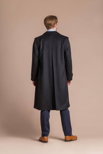 man wearing a black cashmere full length loden overcoat