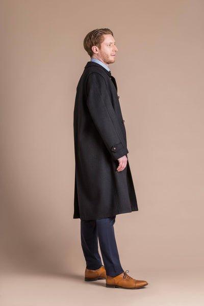 man wearing a black cashmere full length loden coat