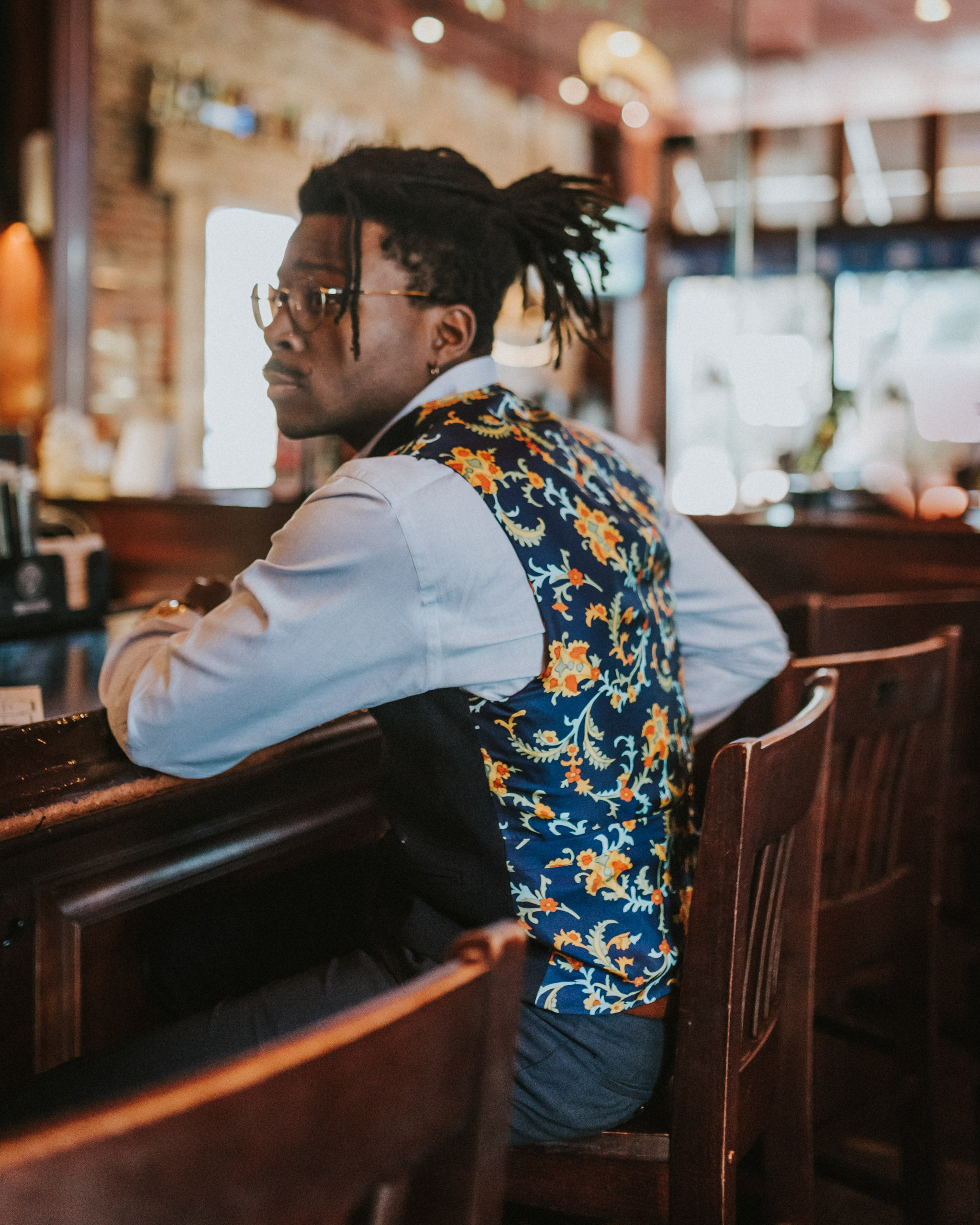 man sitting at a bar wearing a navy blue wool front double breasted shawl collar men's vest with a silk back