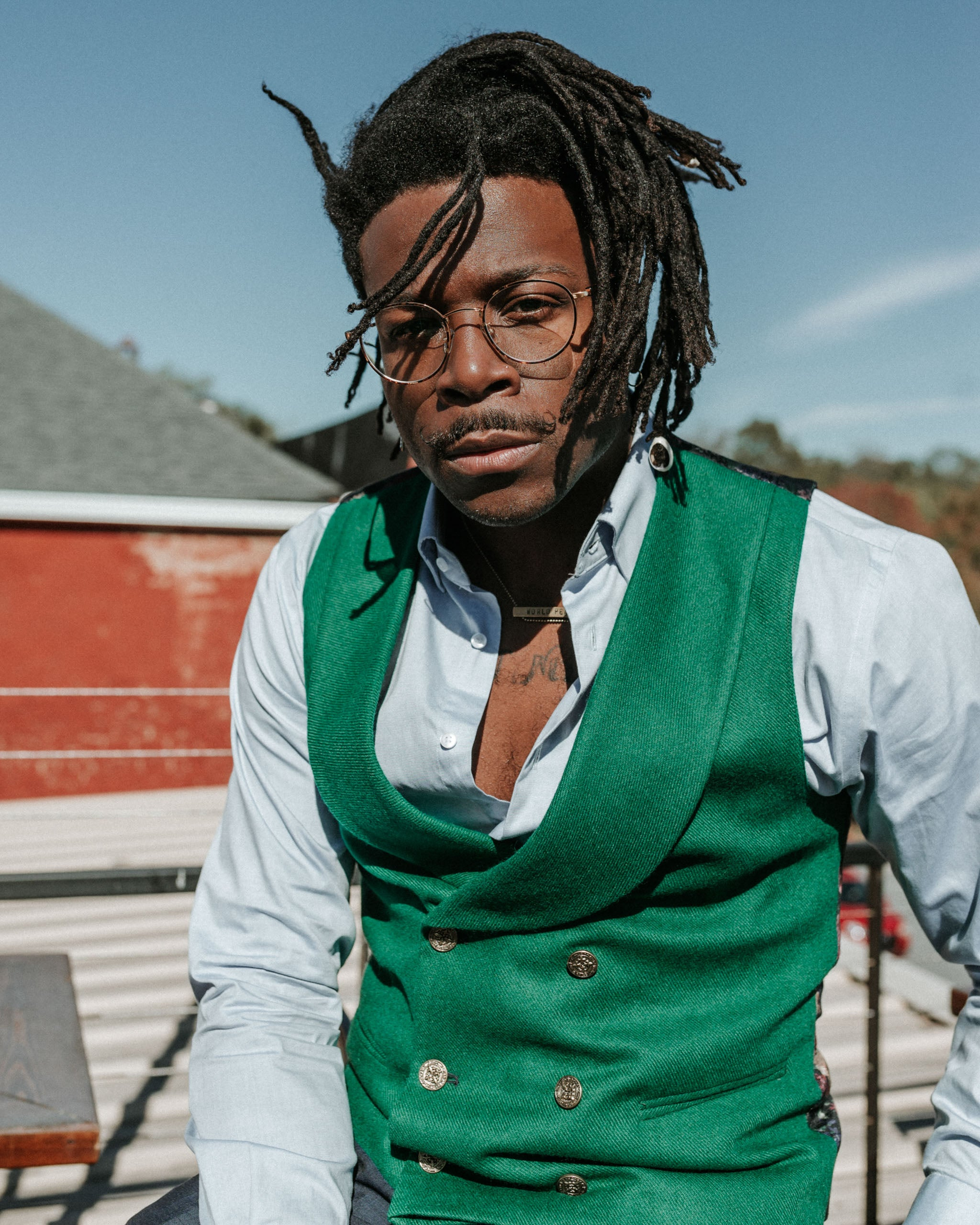 man wearing a green wool front double breasted shawl collar men's vest with gold tone buttons