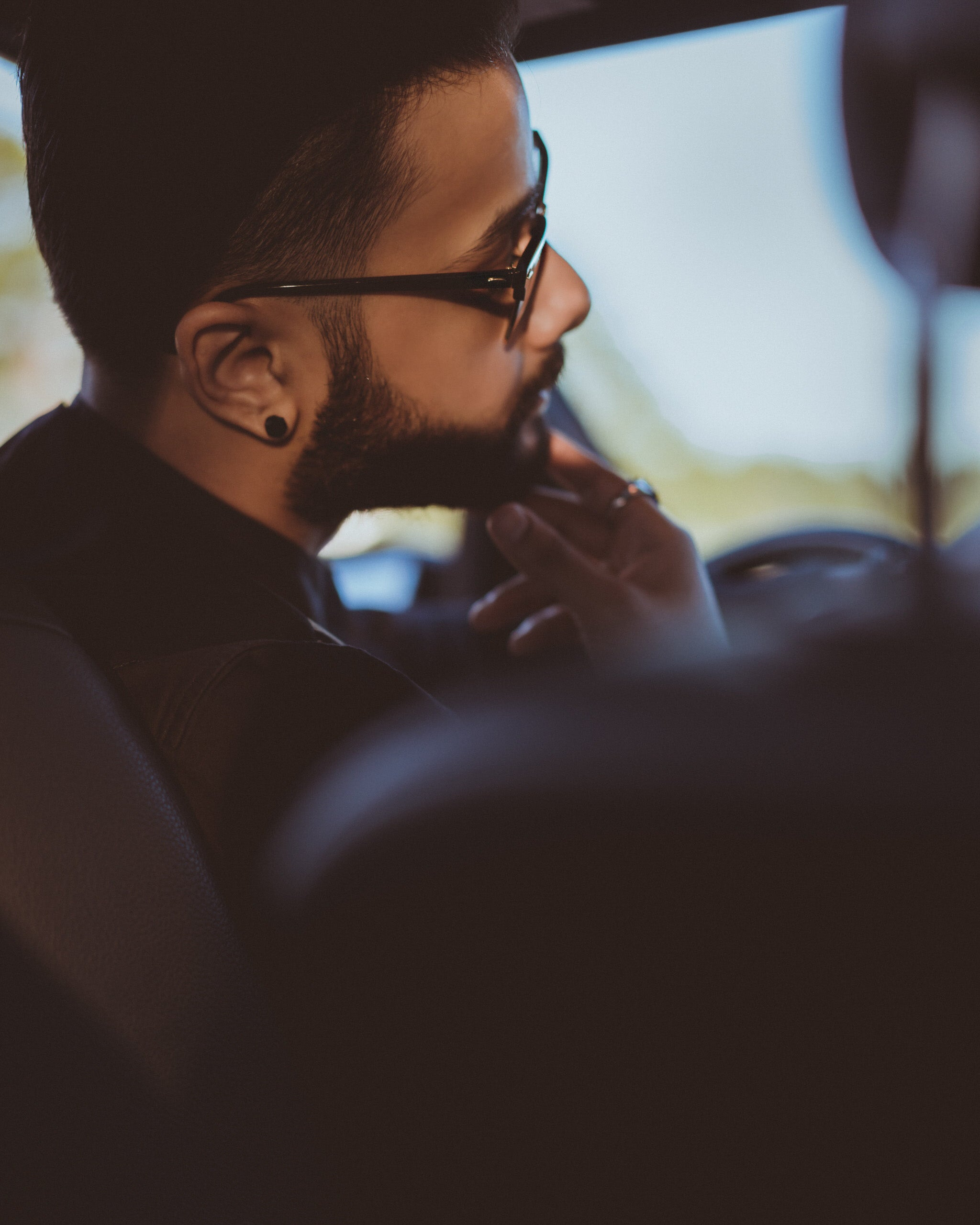 man wearing black sunglasses sitting inside a car