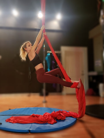 Girl hanging on her Red Aerial Silks
