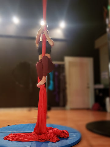 Girl Trying to Climb her Red Aerial Silks