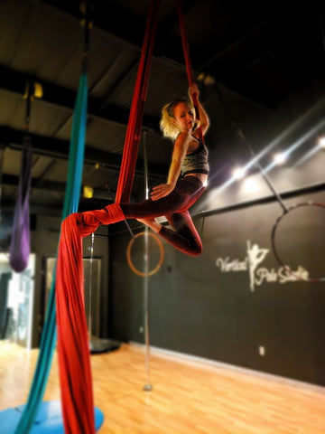 Girl doing a Single Knee Hang in our Red Aerial Silks