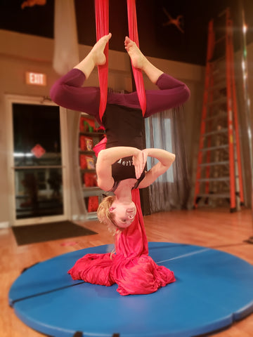 Girl doing a Buddha Pose in our Red Aerial Silks