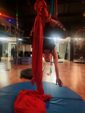 Girl doing a Monkey Pose on our Red Aerial Silks