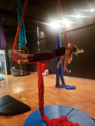 Girl doing a Coffin pose in our Red Aerial Silks