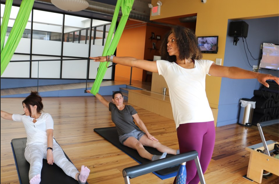 Dragonfly Pilates Aerial Yoga - Students Using Green Yoga Hammocks