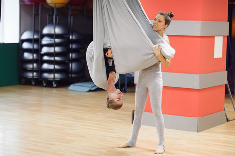 2 girls helping each other out while  practicing aerial yoga