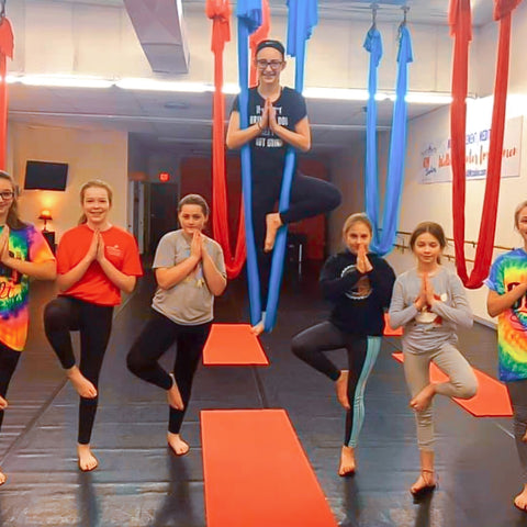 A group of girls doing a tree pose in an aerial yoga studio