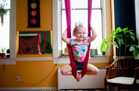 Little Girl Doing an Inverted Butterfly Pose on a Red Aerial Hammock