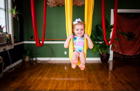 Child Swinging on a Yellow Yoga Hammock